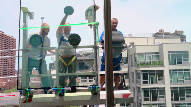 Team of blue-collar workers replacing a broken window in the office building - removing the old broken glass. High-altitude work on the lifting platform which is placed outside. - vídeo
