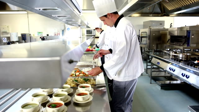 Team of busy chefs working at the order station Team of busy chefs working at the order station in a commercial kitchen commercial kitchen stock videos & royalty-free footage