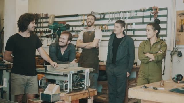 Team of carpenters of a small workshop on a break (slow motion)