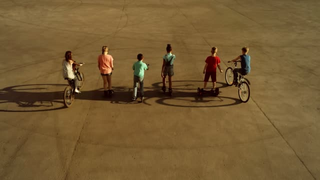 Team of children riding on wheeled vehicles (bicycles, scooters and roller skates) rolling with their back to the camera video