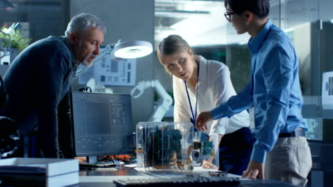 vídeos y material grabado en eventos de stock de equipo de ingenieros informáticos se apoye sobre el escritorio y elija tableros del circuito impreso para trabajar con, computadora muestra programación en curso. en el fondo tecnológicamente había avanzado centro de investigación científica. - desarrollo