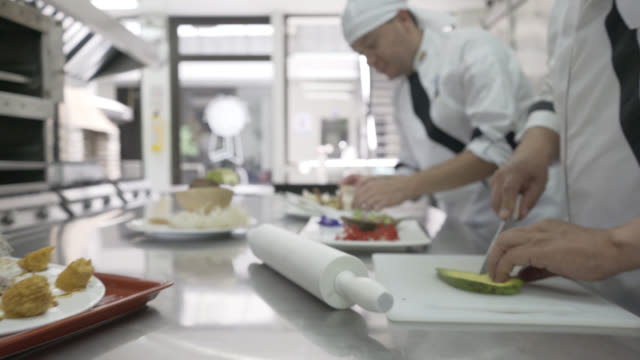 Team of cooking staff preparing a meal working in line