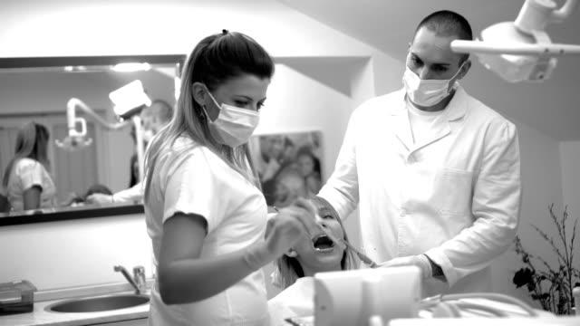 歯科医師のチームは患者の歯を検討します。 - 歯科医師点の映像素材/bロール