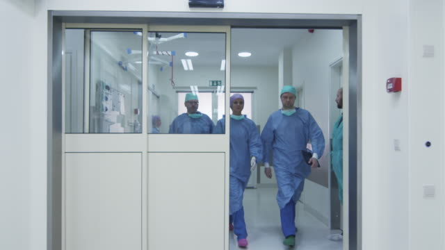 Team of Doctors and Nurses Walking through Hospital Team of Doctors and Nurses Walking through Hospital operating stock videos & royalty-free footage