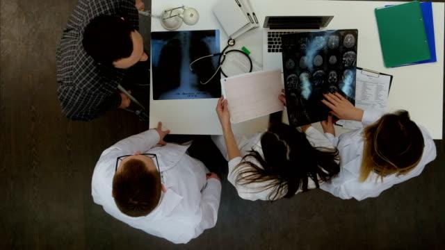Team van artsen xray resultaten uit te leggen aan mannelijke patiënt met krukken video