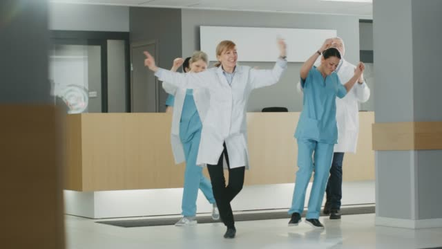 Team of Doctors, Nurses and Assistants Dances After Successful Procedure, They Walk Through the Lobby of the Modern Hospital. Medical Personnel Having Fun.