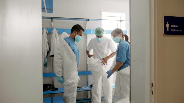 Team of doctors or nurses taking off the protective equipment in hospital changing room after a long day of work