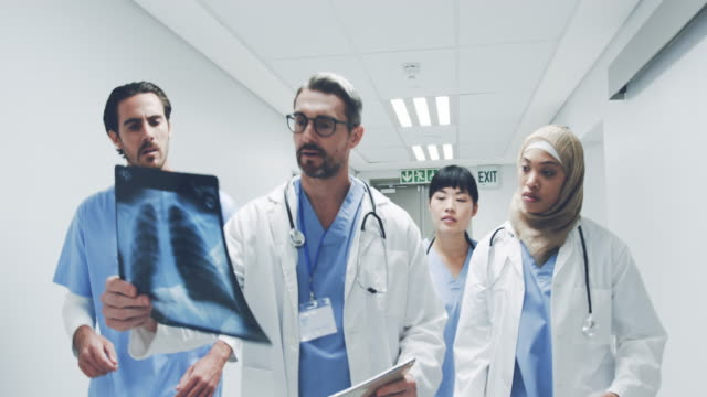 Team of doctors walking in hospital corridor discussing an x-ray and patient notes 4k