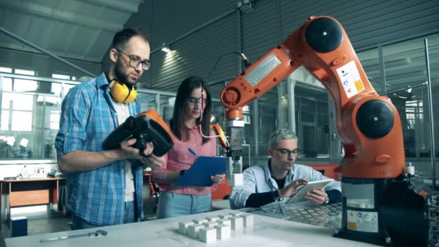 vídeos de stock, filmes e b-roll de equipe de engenheiros estão conduzindo um experimento com robôs - engenheiro