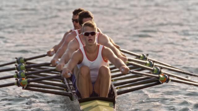 vídeos de stock, filmes e b-roll de slo mo equipe de quatro atletas de remo em um lago ensolarado - remo esporte aquático