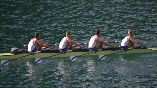 SLO MO Team of four male athletes sculling across a lake Wide handheld shot of a team of four male athletes sculling across a lake on a sunny day. Shot in Slovenia. less than 10 seconds stock videos & royalty-free footage