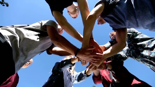 vidéos et rushes de équipe d'amis montrant l'unité joignant les mains - communion
