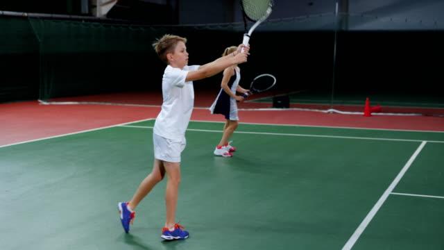 女の子と男の子の屋内コートでテニスのチーム。若い選手の練習 - テニス点の映像素材/bロール