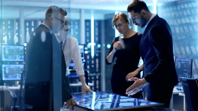 大きなモニターで対話型のテーブル ルームでのコンピューターの完全なタッチ スクリーンの助けを借りて犯罪をトレース政府調査チームは、画面をアニメーション化します。 ビデオ