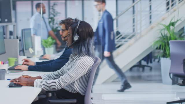 takım yakışıklı ve güzel çeşitli çok kültürlü müşteri hizmetleri operatörleri ile meşgul modern çağrı merkezinde çalışan uzmanları ile kulaklıklar ve aktif aramalar alıyor. - kesit stok videoları ve detay görüntü çekimi