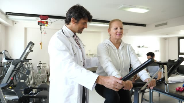 vídeos de stock e filmes b-roll de team of healthcare professionals at a physical recovery clinic each with a patient while doing their therapy all looking happy - melhoria