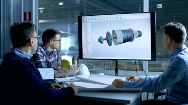 Team of Industrial Engineers Discuss 3D Model of Turbine/ Engine Design Shown on a Presentation Display. In the Background Factory is Seen. video