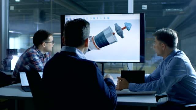 team der wirtschaftsingenieure diskutieren 3d turbine / motor teiledesign auf eine präsentation-display angezeigt. in der hintergrund-fabrik gesehen. - pflicht stock-videos und b-roll-filmmaterial