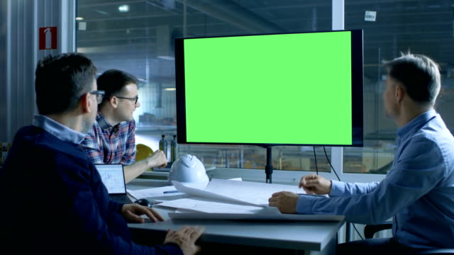 Team of Industrial Engineers Have Important Meeting. Presentation Display Shows Mock-up Green Screen. In the Background Factory is Seen.