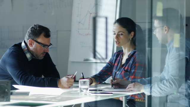 team av industri ingenjörer sitter vid glas konferens bordet, diskuterar pågående projekt. på bordet ser vi ritningar, dokument, komponent prototyper. i bakgrunden whiteboard och ritningar på väggarna. - man architect computer bildbanksvideor och videomaterial från bakom kulisserna