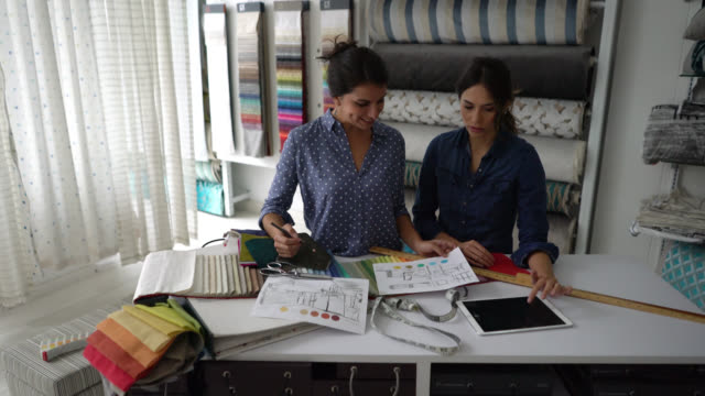 Team of interior designers working on a decor of a room while looking at a plan and a fabric swatch Team of interior designers working on a decor of a room while looking at a plan and a fabric swatch both looking very happy interior designer stock videos & royalty-free footage