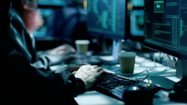 Equipo de internacionalmente querido muchacho y muchacha Hackers organizar ataques de Virus avanzada de servidores corporativos. Lugar es oscuro y tiene múltiples. - vídeo
