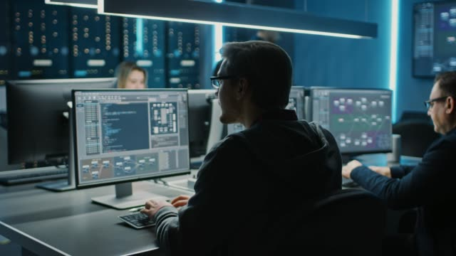 team of it programers working on desktop computers in data center control room. young professionals writing on sophisticated programming code language - усовершенствование стоковые видео и кадры b-roll