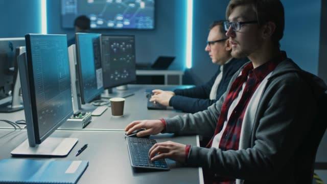 team of it programers working on desktop computers in data center control room. team of young professionals working in software and hardware development, doing coding - man evolution video stock e b–roll