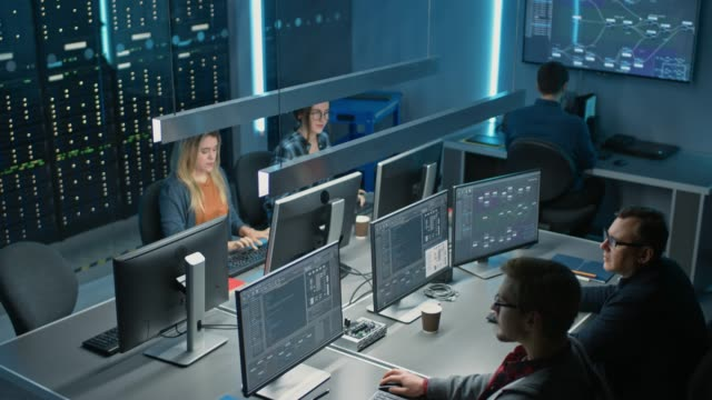 команда ит-программистов, работающих над настольными компьютерами в диспетчерской центра обработки данных. команда молодых специалистов,  - безопасность сети стоковые видео и кадры b-roll