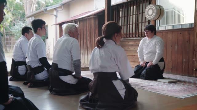 日本の射手チームがひざまずいて話をする - 武道点の映像素材/bロール