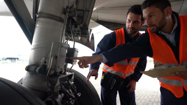 vídeos y material grabado en eventos de stock de equipo de mecánicos haciendo inspección de un avión mirando una lista mientras apuntando a diferentes partes - reparador
