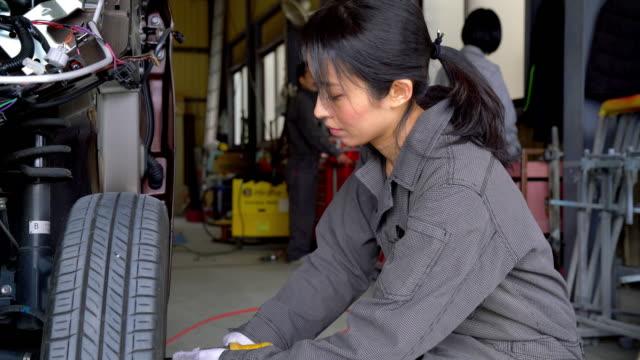 車のガレージで作業を行うメカニックのチーム ビデオ