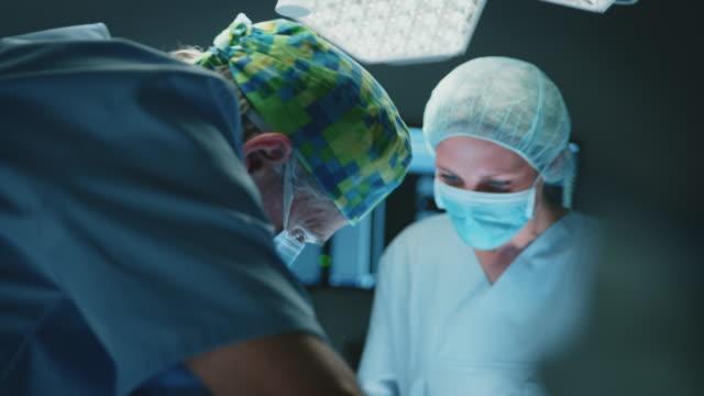vídeos de stock e filmes b-roll de team of medical coworkers operating patient in icu - enfermeira