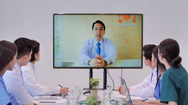 team av läkare på en videokonferenssamtal med en manlig kollega. grupp unga praktikanter lyssnar på läkares föreläsning under läkar konferensen. högteknologiska möten, hälsovård, medicinsk pedagogik, människor och medicin koncept. utbildning ä - videor med medicinsk undersökning bildbanksvideor och videomaterial från bakom kulisserna