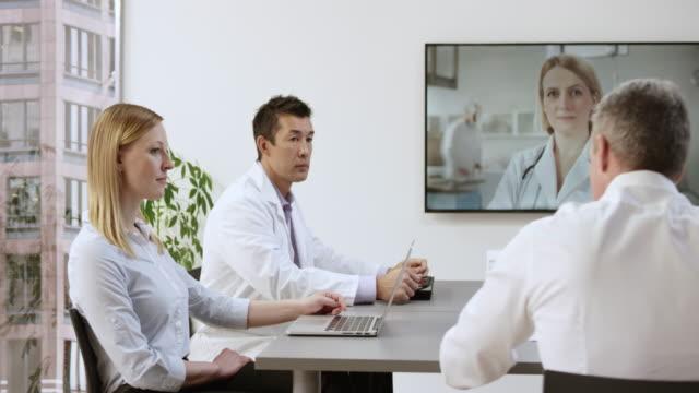 team von ärzten auf eine videokonferenz-aufruf mit einer kollegin - konferenztisch stock-videos und b-roll-filmmaterial