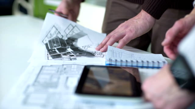 Royalty free blueprint paper hd video 4k stock footage b roll team of professional engineers working with blueprints video malvernweather Gallery