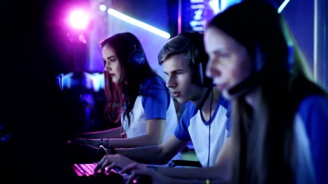 ゲーマーに競争力のあるビデオ ゲーム サイバーのゲーム大会にプロの esport のチーム。女の子と男の子があるヘッドフォンでは、ネオンの明かりでアリーナが点灯しています。 - ゲーム ヘッドフォン点の映像素材/bロール