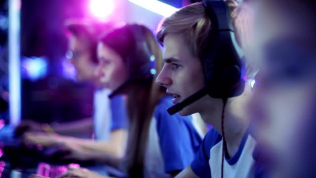 ゲーマーがサイバーのゲーム大会のビデオ ゲームで遊ぶプロ esport のチーム。彼らは互いにマイクに向かって話します。アリーナはネオンの光にクールに見えます。 - ゲーム ヘッドフォン点の映像素材/bロール