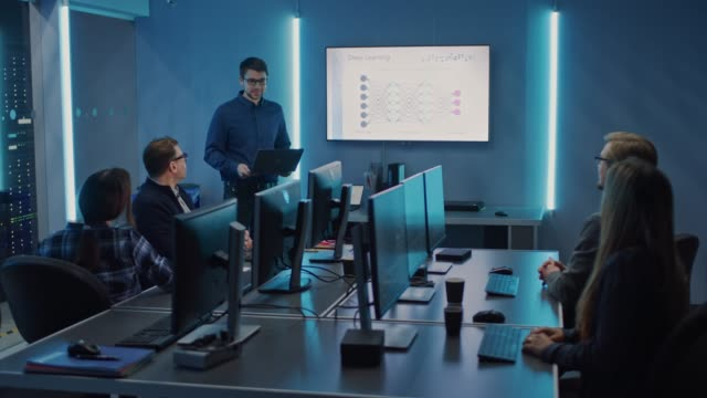 Video Team of Professional IT Developers Have a Meeting, Speaker Talks about New Blockchain Based Software Development Shown on TV. Concept: Software Development, Deep Learning, Artificial Intelligence, Data Mining