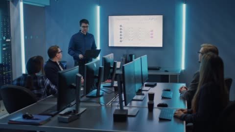vidéos et rushes de équipe de professionnels de l'informatique ont une réunion, conférencier parle de nouveau développement de logiciels basés sur la blockchain montré à la télévision. concept: développement de logiciels, apprentissage profond, intelligence artifici - en rang