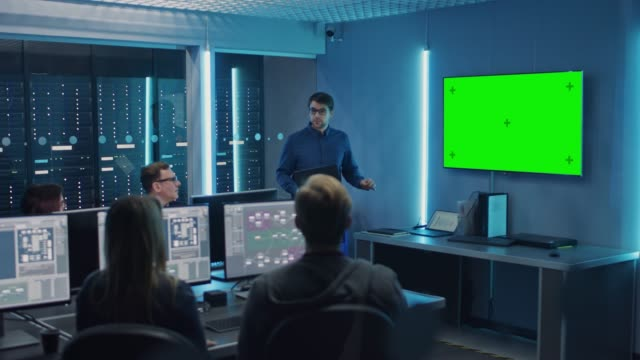 Team of Professional IT Developers Have a Meeting, Speaker Talks about About New Concepts, On Wall TV has Green Mock-up Screen. Concept: Software Development, Deep Learning, Artificial Intelligence, Data Mining