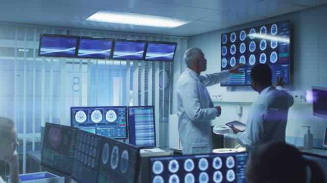 専門医療の科学者のチームは、脳研究所で働きます。神経科/神経科学者のモニターに囲まれて示す ct、mri スキャンは議論を持つとパソコンに取り組んで。 - mri検査点の映像素材/bロール