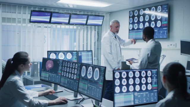 Team of Professional Scientists Work in the Brain Research Laboratory. Neurologists / Neuroscientists Surrounded by Monitors Showing CT, MRI Scans Having Discussions and Working on Personal Computers.