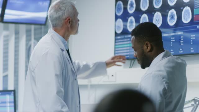 専門の科学者のチームは、脳研究所で働きます。神経科/神経科学者のモニターに囲まれて示す ct、mri スキャンは議論すること、パソコンに取り組んで。 - mri検査点の映像素材/bロール
