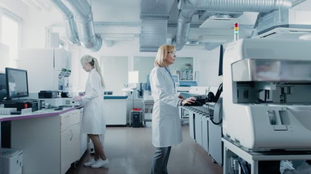 医療機器のコンピューターに取り組んで、血と近代的な研究室の特別なマシンと遺伝的物質的なサンプルの分析の研究者のチーム。 - lab点の映像素材/bロール