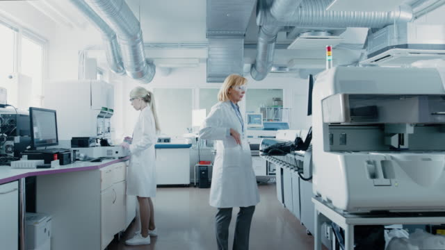 team of research scientists working on computer, with medical equipment, analyzing blood and genetic material samples with special machines in the modern laboratory. - figura femminile video stock e b–roll