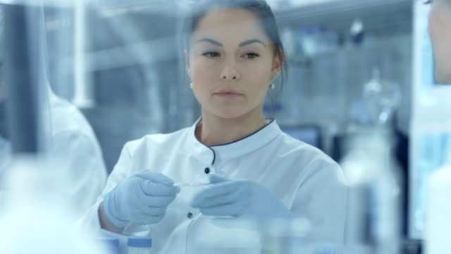 Team of Research Scientists Working With Microscope, Assistant Passes on Slides with Samples to a Chief Scientist and She Looks at them Under Microscope. They Work in a Modern Laboratory/ Medical Center. video