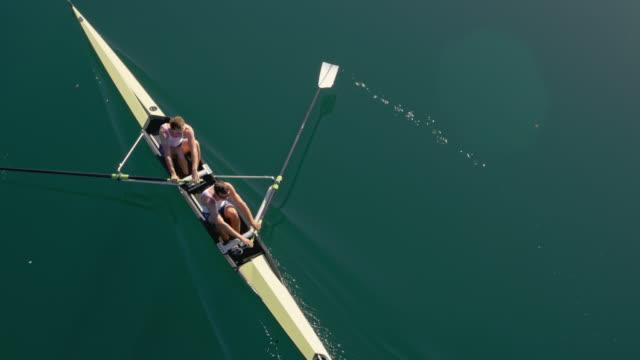 vídeos de stock, filmes e b-roll de equipe aérea de remadores em um remo deslizando sobre um lago ensolarado - remo atividade física