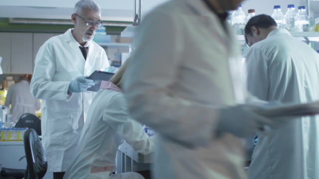 Team of scientists in white coats are working with a laptop and tablet in a laboratory. video