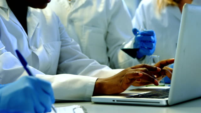 Team of scientists working in laboratory 4k